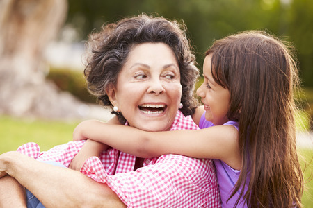 hispanic girls: Grandmother And Granddaughter Sitting In Park Together Stock Photo