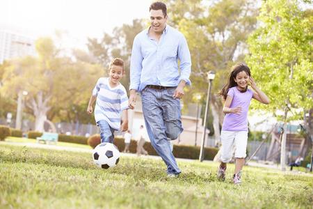 公園でサッカーを一緒に子供と父親 写真素材