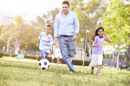 jugando futbol: Padre con los ni�os que juegan a f�tbol en el parque Juntos Foto de archivo