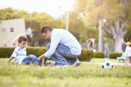family in park: Father Looking After Son Injured Playing Football