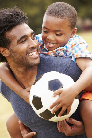 afroamericanas: Padre con el hijo que juega a fútbol en el parque Juntos
