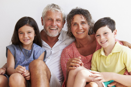 grandparents: Portrait Of Grandparents With Grandchildren Sitting By Wall