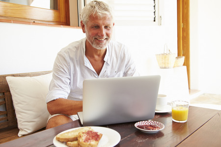 hombres maduros: Hombre maduro sentado en mesa de desayuno Usar el portátil