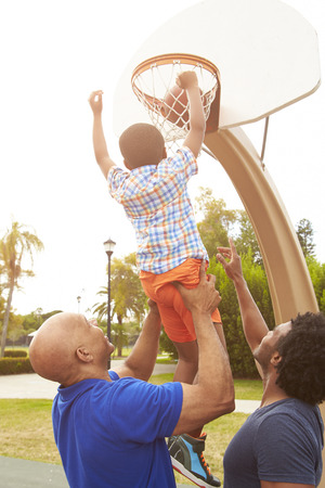 family playing: Grandfather With Son And Grandson Playing Basketball Stock Photo