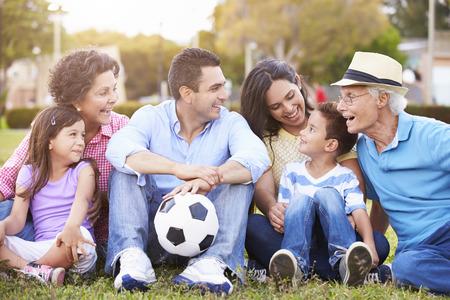 niños jugando en el parque: Multi generacional que juega a fútbol Juntos