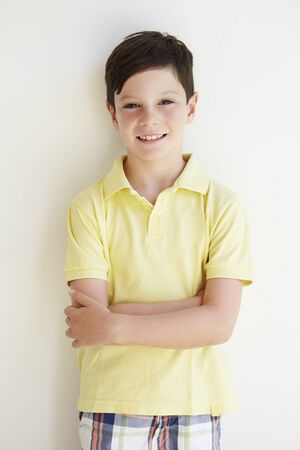 7 years old: Smiling Young Boy Standing Outdoors Against White Wall