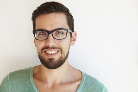 specs: Portrait Of Young Man Standing Outdoors Against White Wall
