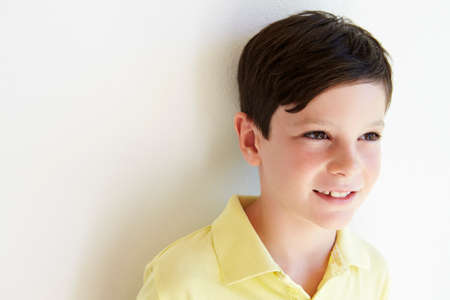 white wall: Smiling Young Boy Standing Outdoors Against White Wall