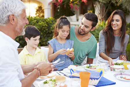 family with three children: Multi Generation Family Eating Meal At Outdoors Together