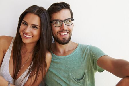 white wall: Portrait Of Couple Sitting Against White Wall Stock Photo