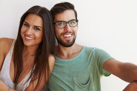 persona alegre: Retrato de pares que se sienta contra la pared blanca