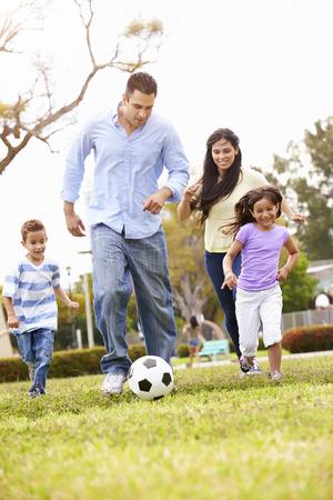 niños jugando en el parque: Familia hispánica que juega a fútbol Juntos Foto de archivo