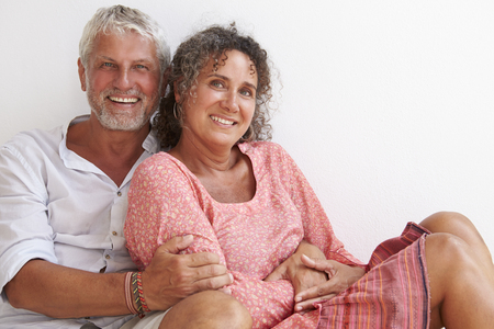 white men: Portrait Of Loving Mature Couple Sitting Against Wall
