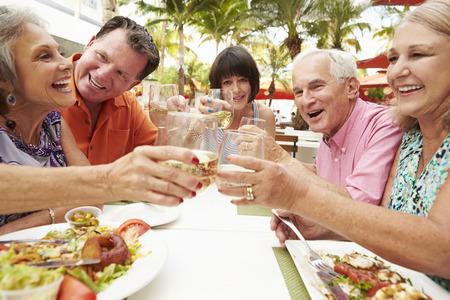 retirement happy man: Group Of Senior Friends Enjoying Meal In Outdoor Restaurant Stock Photo