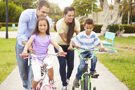 hispanic family: Parents Teaching Children To Ride Bikes In Park