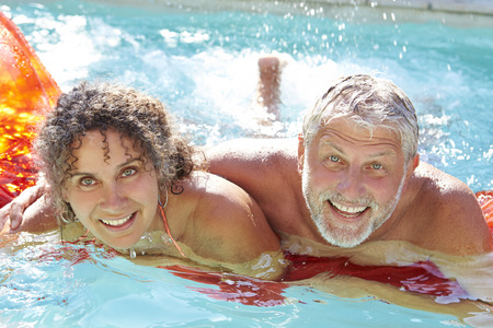 splash pool: Mature Couple Relaxing On Airbed In Swimming Pool Stock Photo