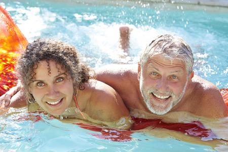 hombres maduros: Pareja madura que se relaja en cama de aire en piscina Foto de archivo