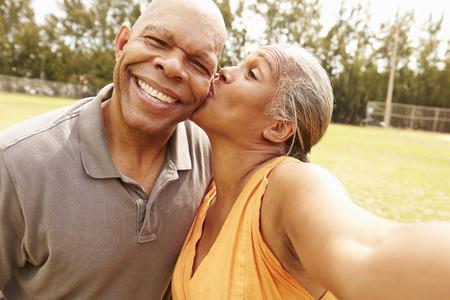 besos hombres: Senior pareja romántica Tomando selfie En el Parque