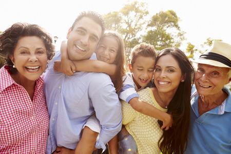 familias unidas: Multi generacional que se divierten en jardín junto