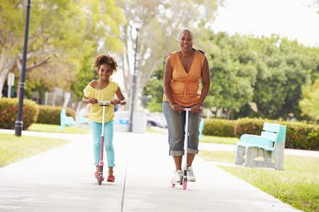 abuelos: Abuela y nieta Riding Scooters en parque Foto de archivo