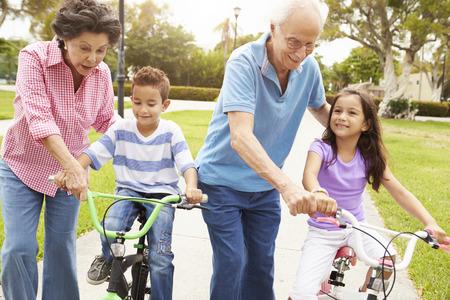 Abuelos Nietos Enseñanza andar en bicicleta en el parque Foto de archivo - 42314904