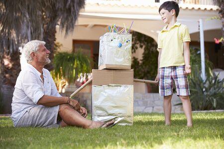 Niños ayudando: Abuelo y nieto Edificio Modelo Robot En Jardín