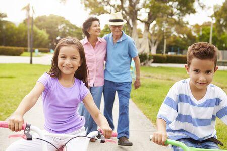 abuelos: Abuelos Nietos Tomar andar en bicicleta en el parque Foto de archivo