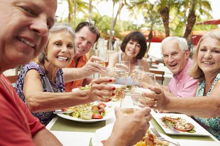 grupos de personas: Grupo de amigos mayores que disfrutan de la comida en restaurante al aire libre