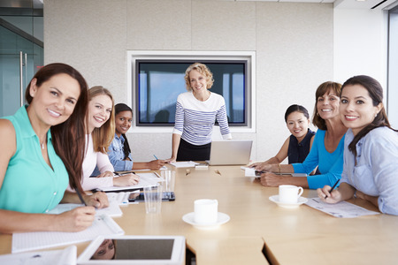 group cooperation: Group Of Businesswomen Meeting Around Boardroom Table