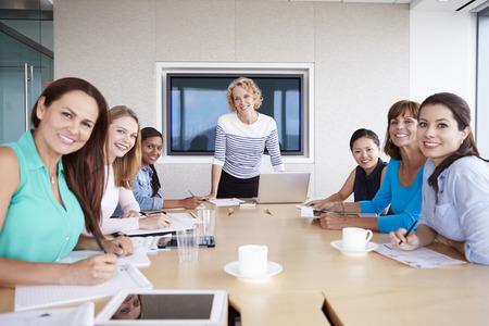 Skupina podnikatelky hromady kolem zasedací místnosti tabulce