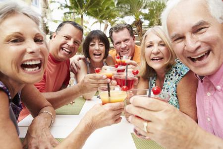 senior group: Group Of Senior Friends Enjoying Cocktails In Bar Together