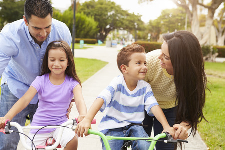 father teaching daughter: Parents Teaching Children To Ride Bikes In Park