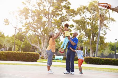 niños jugando: Abuelos y nietos que juegan a baloncesto Juntos Foto de archivo