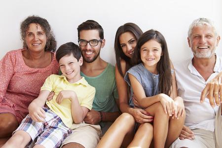 Multi Generation Family Sitting Against Wall Foto de archivo