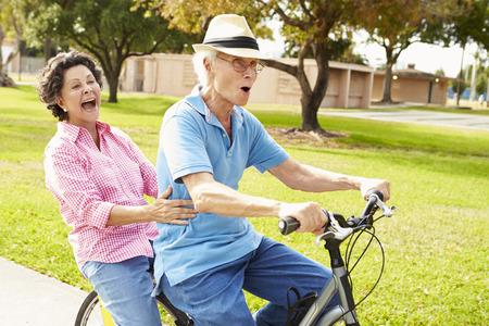 Seniors hispaniques vélos Couple d'équitation dans le parc