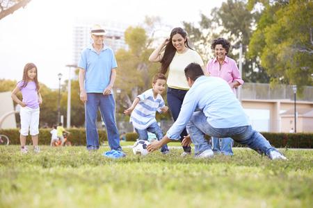 Multi Generation Family Playing Soccer Samen Stockfoto