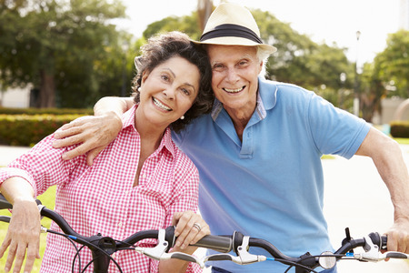 happy senior couple: Senior Hispanic Couple Riding Bikes In Park