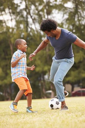 familias felices: Padre con el hijo que juega a fútbol en el parque Juntos