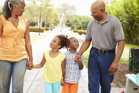 祖父母が孫を公園を歩いて