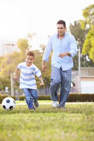 Padre con el hijo que juega a fútbol en el parque Juntos