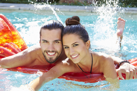 splash pool: Portrait Of Young Couple Relaxing In Swimming Pool Stock Photo