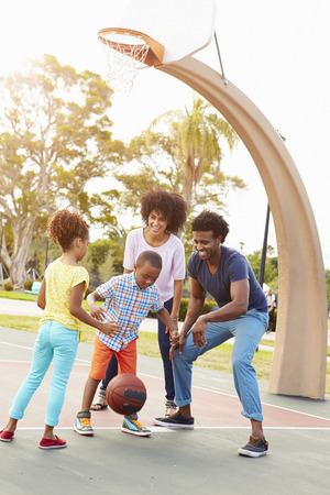 outdoor basketball court: Family Playing Basketball Together Stock Photo