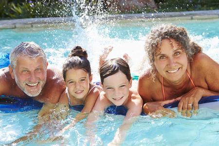 Grootouders met kleinkinderen op luchtbed in het zwembad
