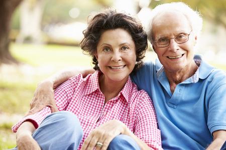 ancianos felices: Pares hispánicos mayores que se sientan en parque junto