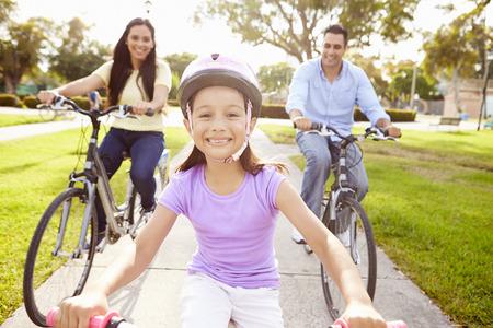 公園で娘の乗馬のバイクを持つ親 写真素材