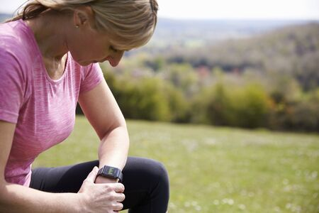 Mature Woman Checking Activity Tracker Whilst On Run