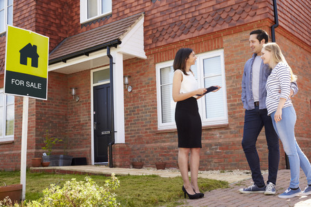 Realtor Outside House For Sale With Young Couple