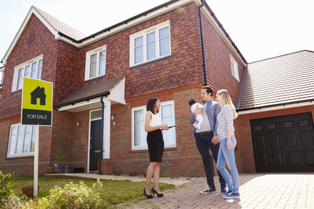 viewing: Realtor Outside House For Sale With Young Family