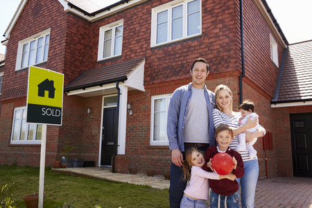 3 6 months: Portrait Of Family Outside New Home With Sold Sign