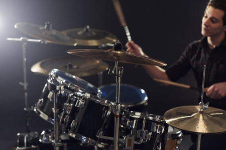 Side View Of Young Drummer Playing Drum Kit In Studio 版權商用圖片